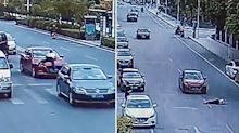 The shocking moment a wife drives down road with husband on her bonnet