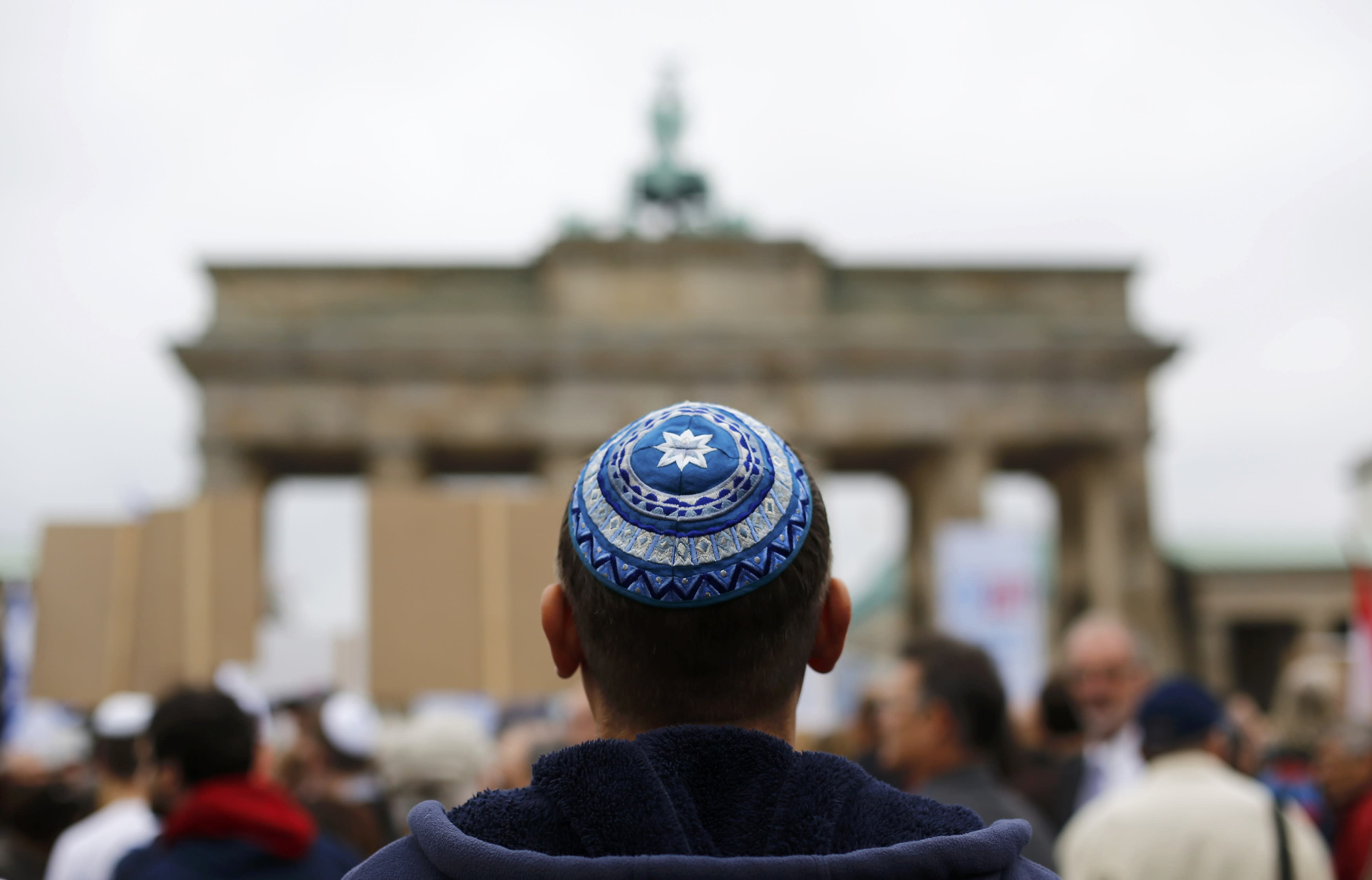 A man wearing a kippah waits for the start of an anti-Semitism demo at Berlin's Brandenburg Gate September 14, 2014. Placard reads ' Never again'. REUTERS/Thomas Peter (GERMANY - Tags: POLITICS)
