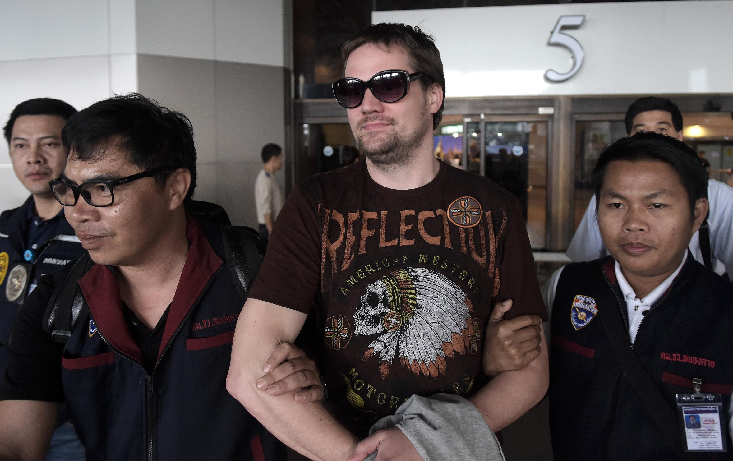 Thai police escort Pirate Bay co-founder Fredrik Neij (centre) from Don Mueang airport to an immigration detention centre in Bangkok, on November 5, 2014 (AFP Photo/Nicolas Asfouri)