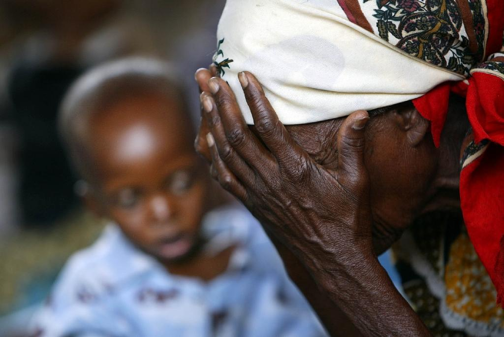 A Malawian grandmother rests on October 14, 2005, close to her malnoureshed grandson in Zomba (AFP Photo/Gianluigi Guercia)