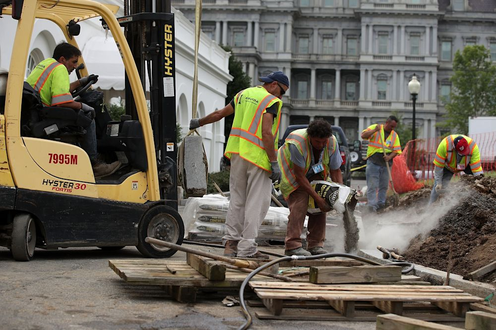 Workers of M&F Concrete pour concrete as they install granite curb on the ground of the White House in front of the West Wing August 8, 2017 in Washington, DC. (Photo by Alex Wong/Getty Images)