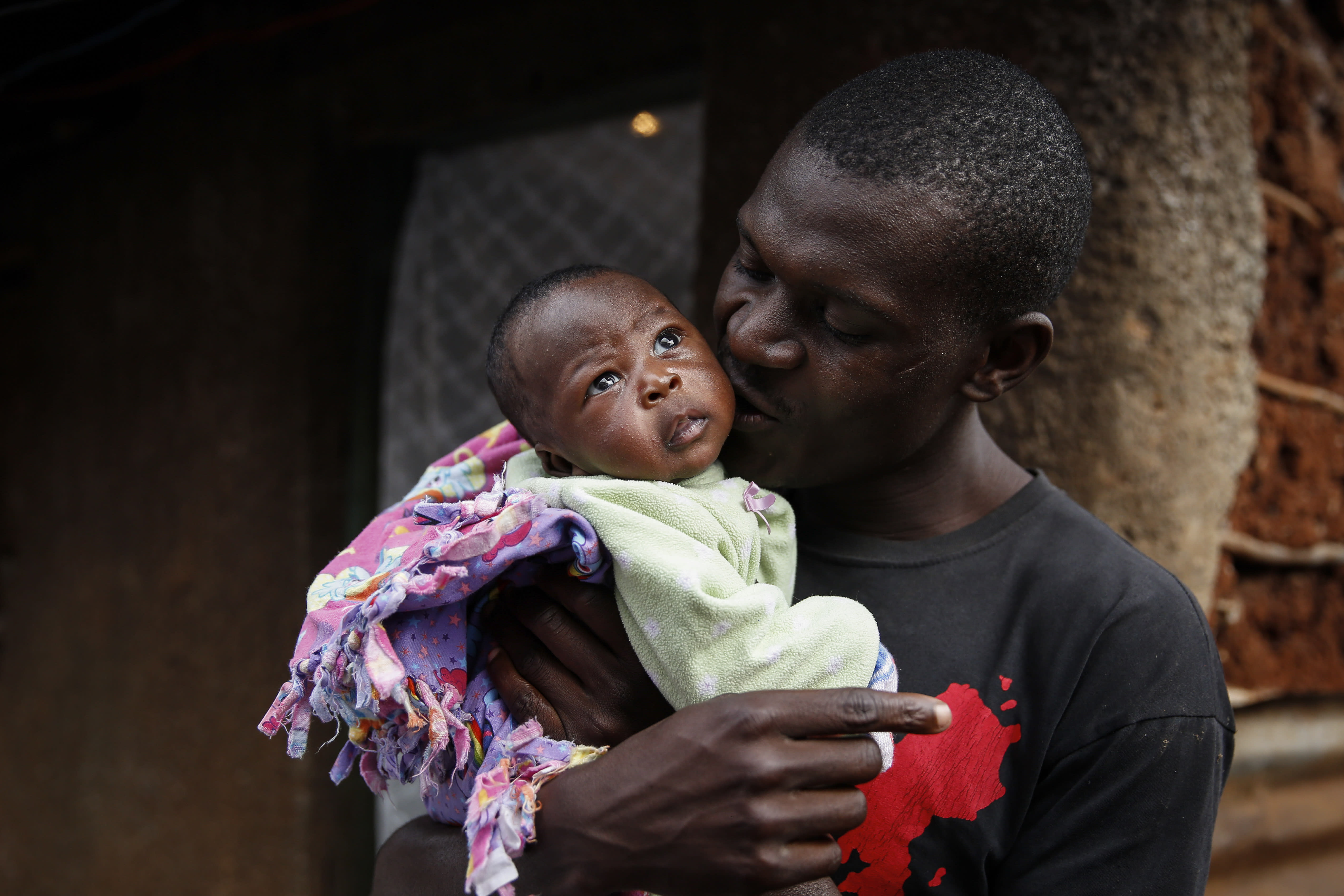 Gabriel Owour Juma holds his daughter Shaniz Joy Juma, delivered a month earlier by a traditional birth attendant during a dusk-to-dawn curfew, in the Kibera slum of Nairobi, Kenya Friday, July 3, 2020. Kenya already had one of the worst maternal mortality rates in the world, and though data are not yet available on the effects of the curfew aimed at curbing the spread of the coronavirus, experts believe the number of women and babies who die in childbirth has increased significantly since it was imposed mid-March. (AP Photo/Brian Inganga)