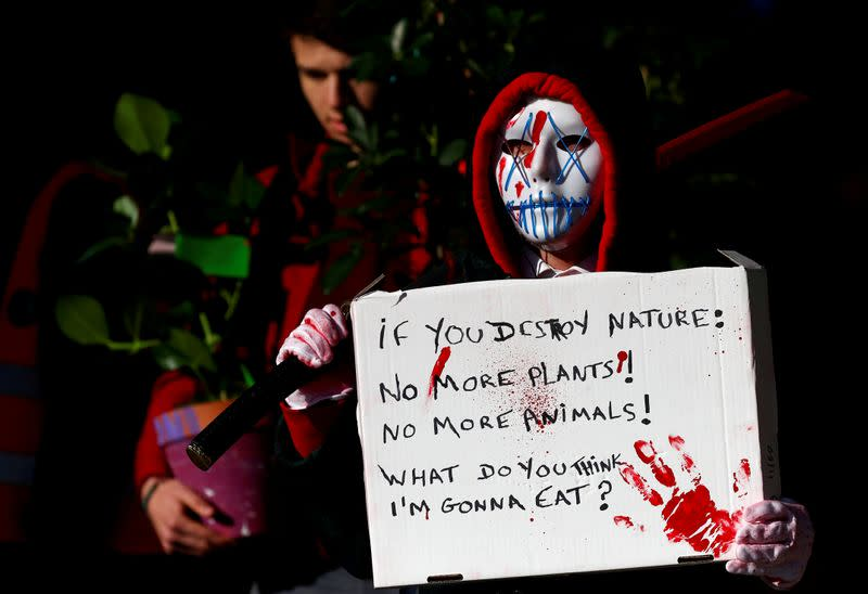 FILE PHOTO: A climate activist holds a sign during a protest in front of EU Commission headquarters in Brussels