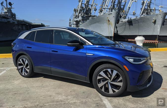 A blue Volkswagen ID.4 EV is parked in a lot right next to San Francisco docks with military ships.