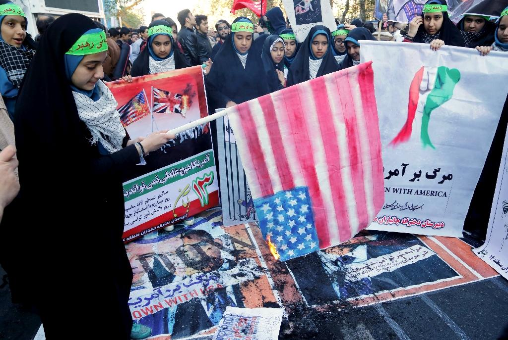 An Iranian youth burns home-made American flag outside the former US embassy Tehran on November 3, 2016 (AFP Photo/Atta Kenare)