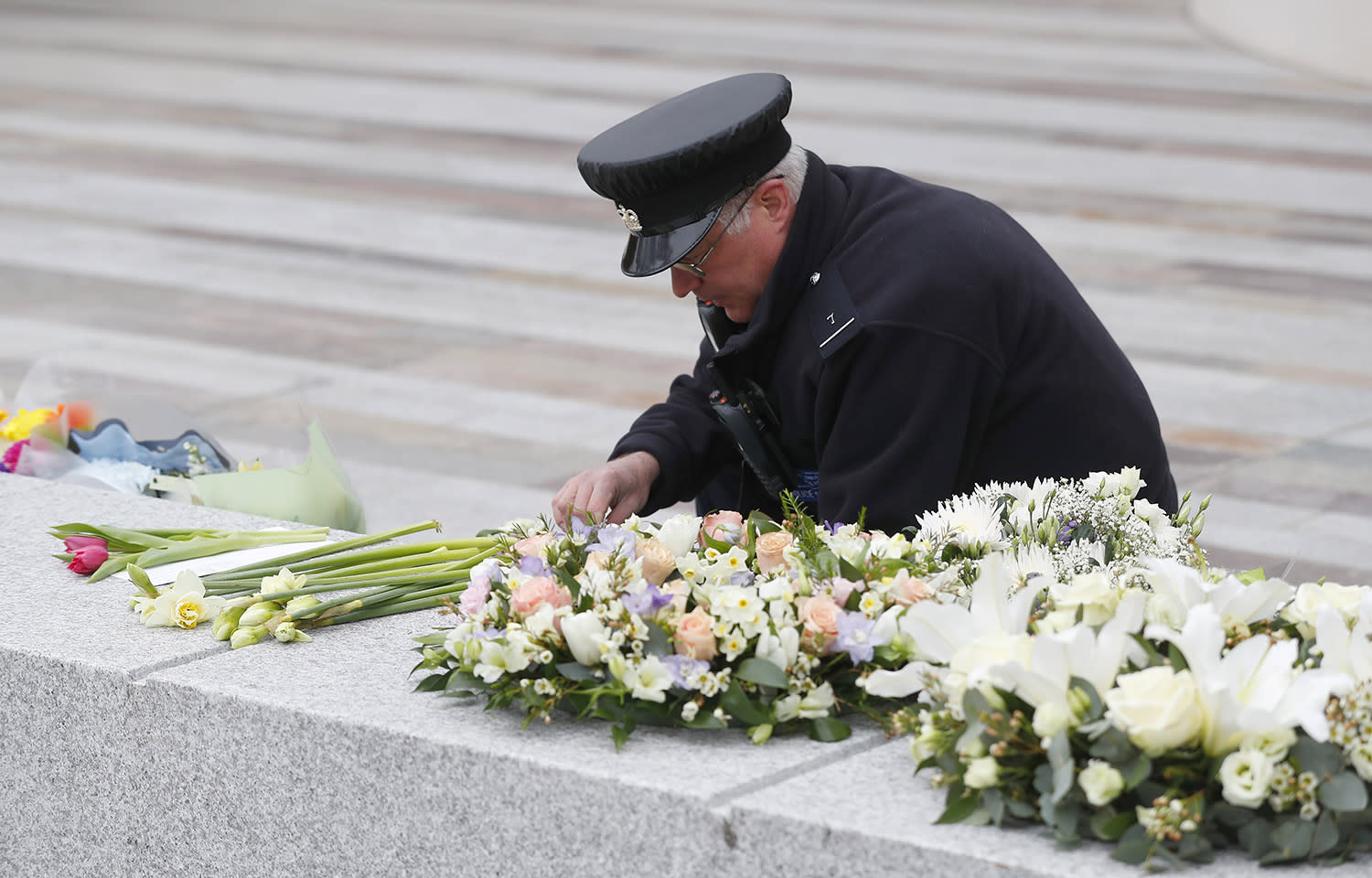 <p>A security officer arranges flowers outside New Scotland Yard following Wednesday's attack outside the Houses of Parliament in London, Friday, March 24, 2017. (Peter Nicholls/Reuters) </p>