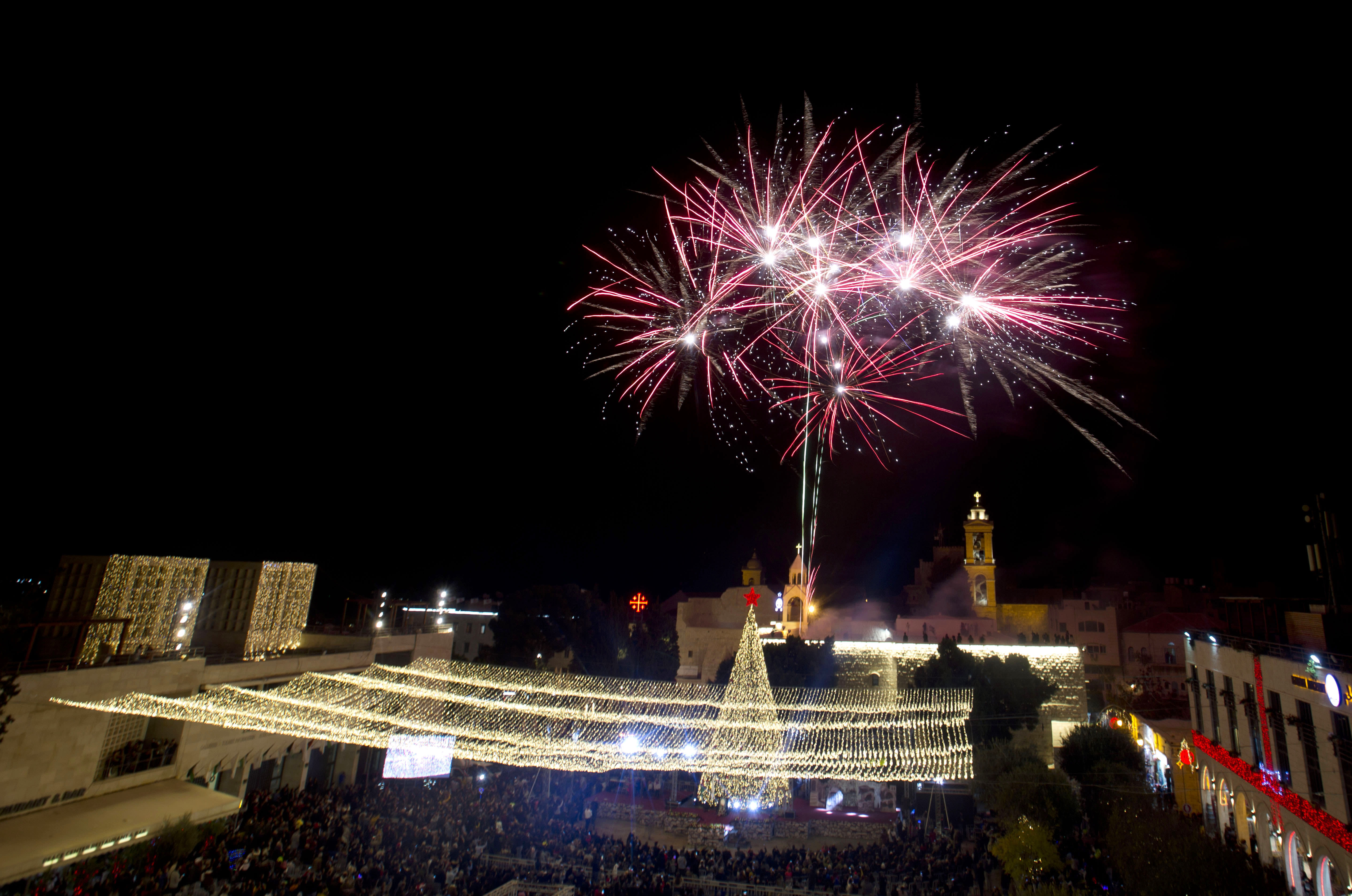 Palestinian Christians celebrate the lighting of a Christmas tree outside the Church of the Nativity, traditionally believed by Christians to be the birthplace of Jesus Christ in the West Bank city of Bethlehem, Saturday, Nov. 30, 2019. (AP Photo/Majdi Mohammed)
