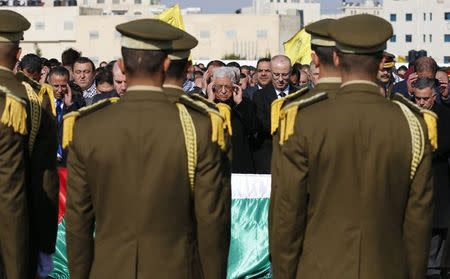 Palestinian President Mahmoud Abbas (C) prays next to the coffin of Palestinian minister Ziad Abu Ein during his funeral in the West Bank city of Ramallah December 11, 2014. REUTERS/Ammar Awad