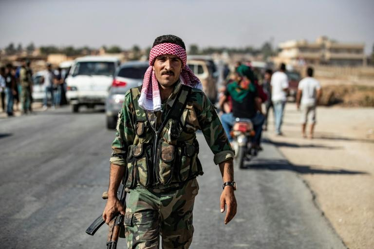 Syrian regime forces patrol a street at the western entrance to the town of Tal Tamr in northeast Syria's Hasakeh province