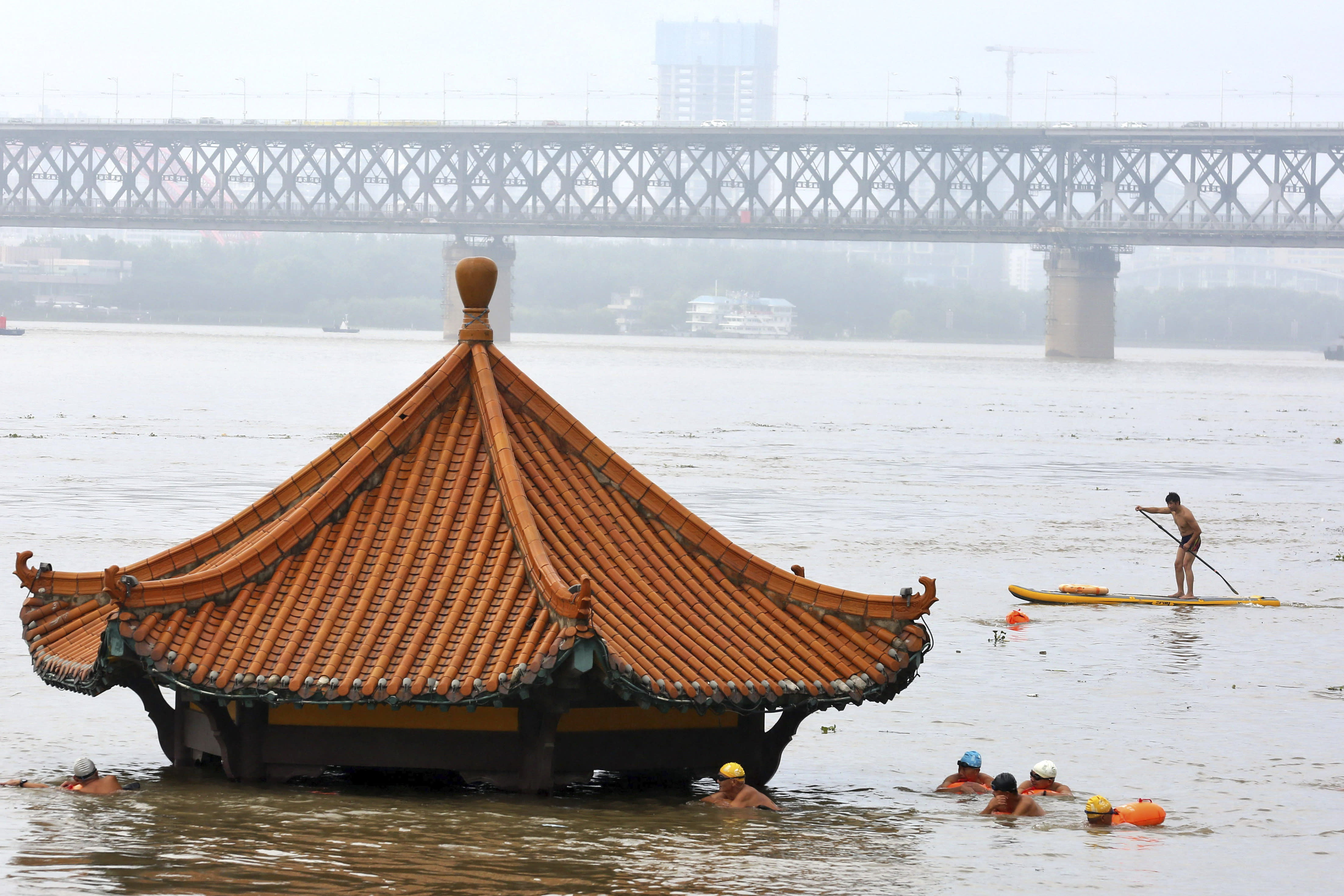 Residents swim past a riverside pavilion submerged by the flooded Yangtze River in Wuhan in central China's Hubei province Wednesday, July 8, 2020. Rescuers in central China were searching Wednesday for people left missing in a landslide triggered amid widespread flooding across much of the country. (Chinatopix Via AP)