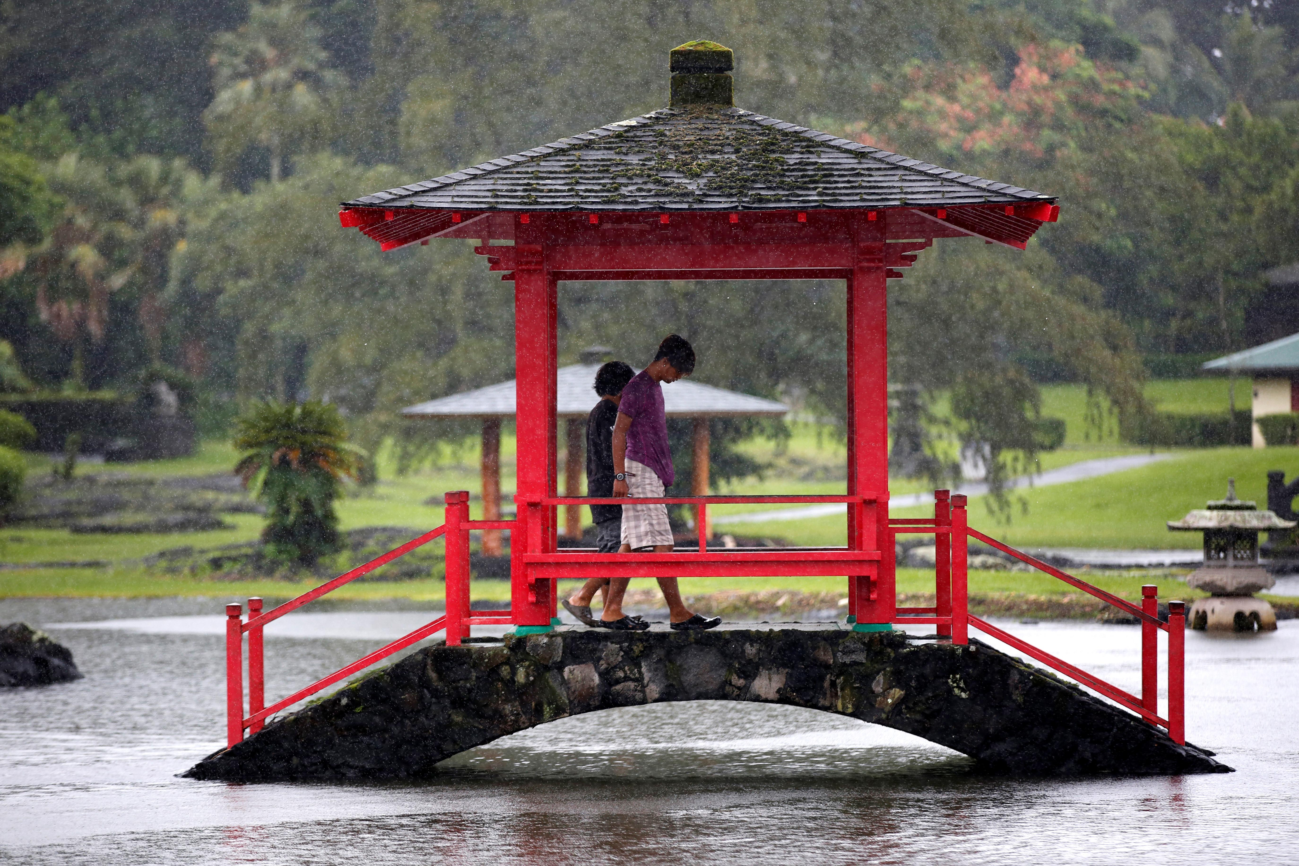 <p>Two men walk through a park flooded by rain from Hurricane Lane in Hilo, Hawaii, Aug. 25, 2018. (Photo: Terray Sylvester/Reuters) </p>