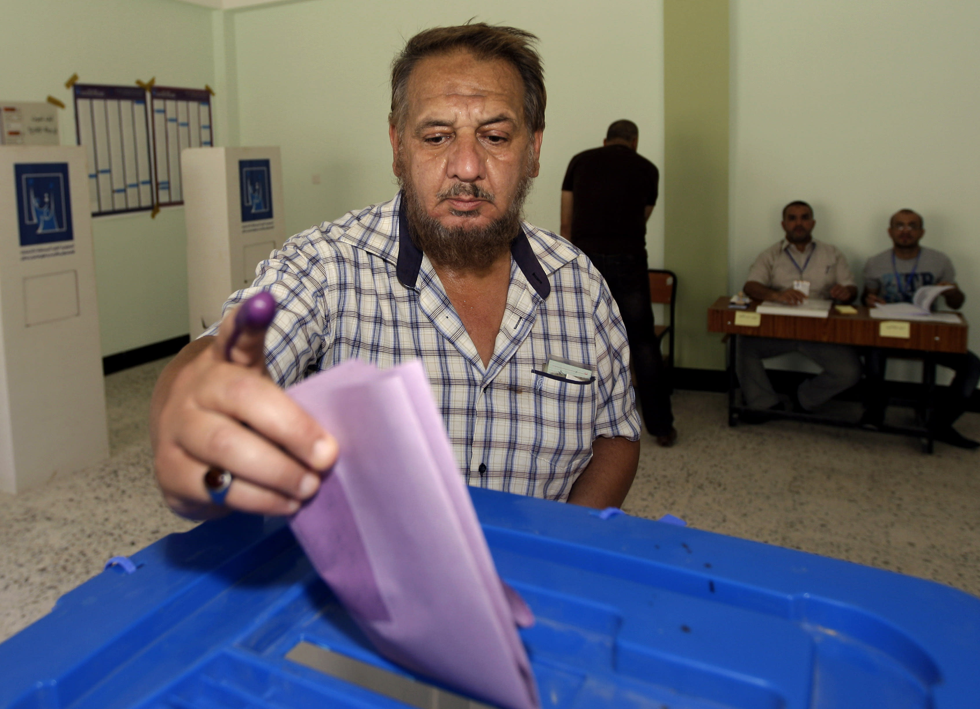 An Iraqi man casts his ballot at a polling center during the country's provincial elections in Fallujah, Iraq, Thursday, June 20, 2013. Iraqis in two Sunni-dominated provinces voted Thursday in provincial elections marked by tight security measures that left streets in former insurgent strongholds largely deserted. (AP Photo/Khalid Mohammed)