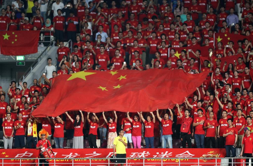 Chinese football fans hold their national flag as they listen to their national anthem