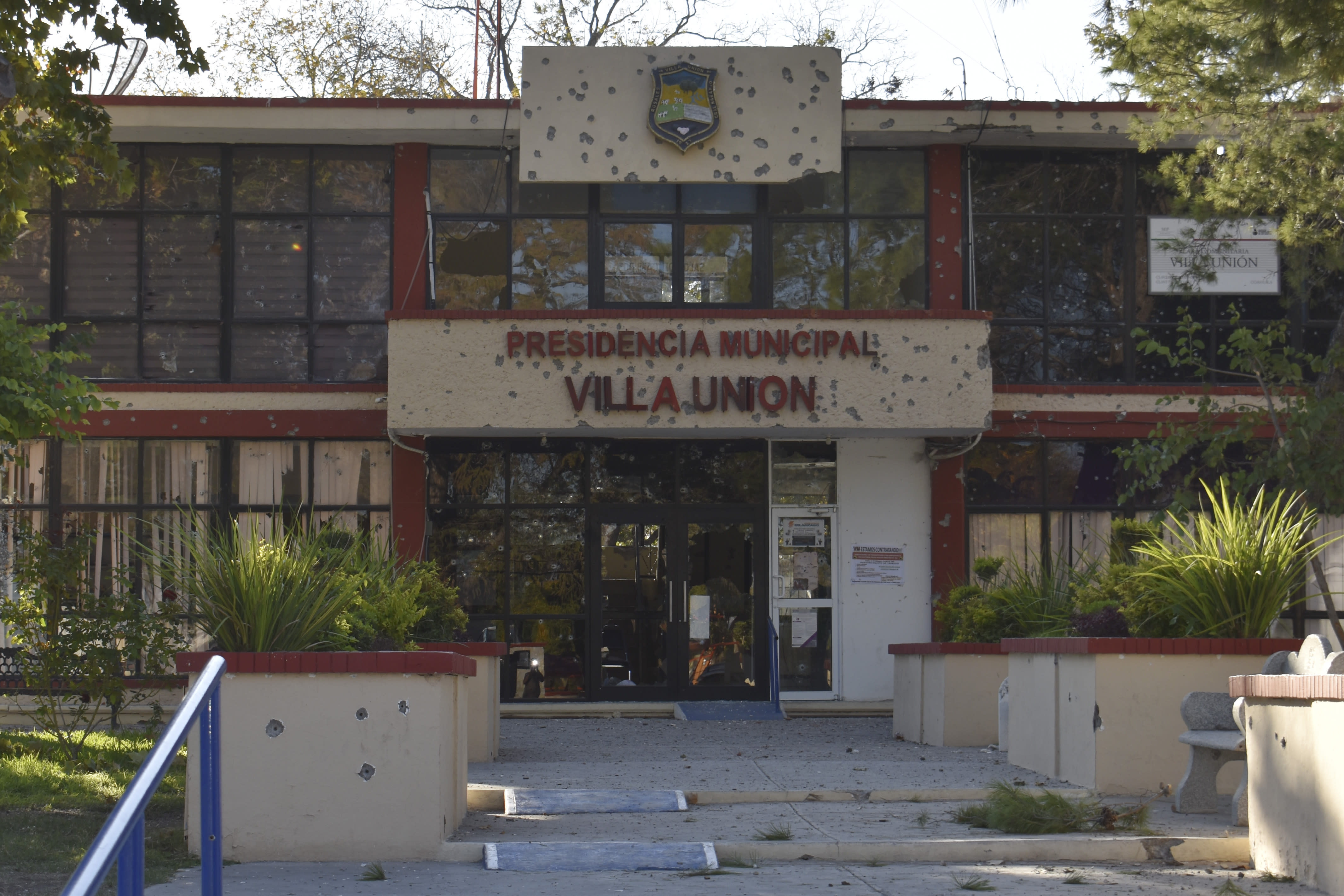 The City Hall of Villa Union is riddled with bullet holes after a gun battle between Mexican security forces and suspected cartel gunmen, Saturday, Nov. 30, 2019. At least 14 people were killed, four of them police officers, after an armed group in a convoy of trucks stormed the town, in Coahuila state, prompting security forces to intervene, state Gov. Miguel Riquelme Solis said. (AP Photo/Gerardo Sanchez)