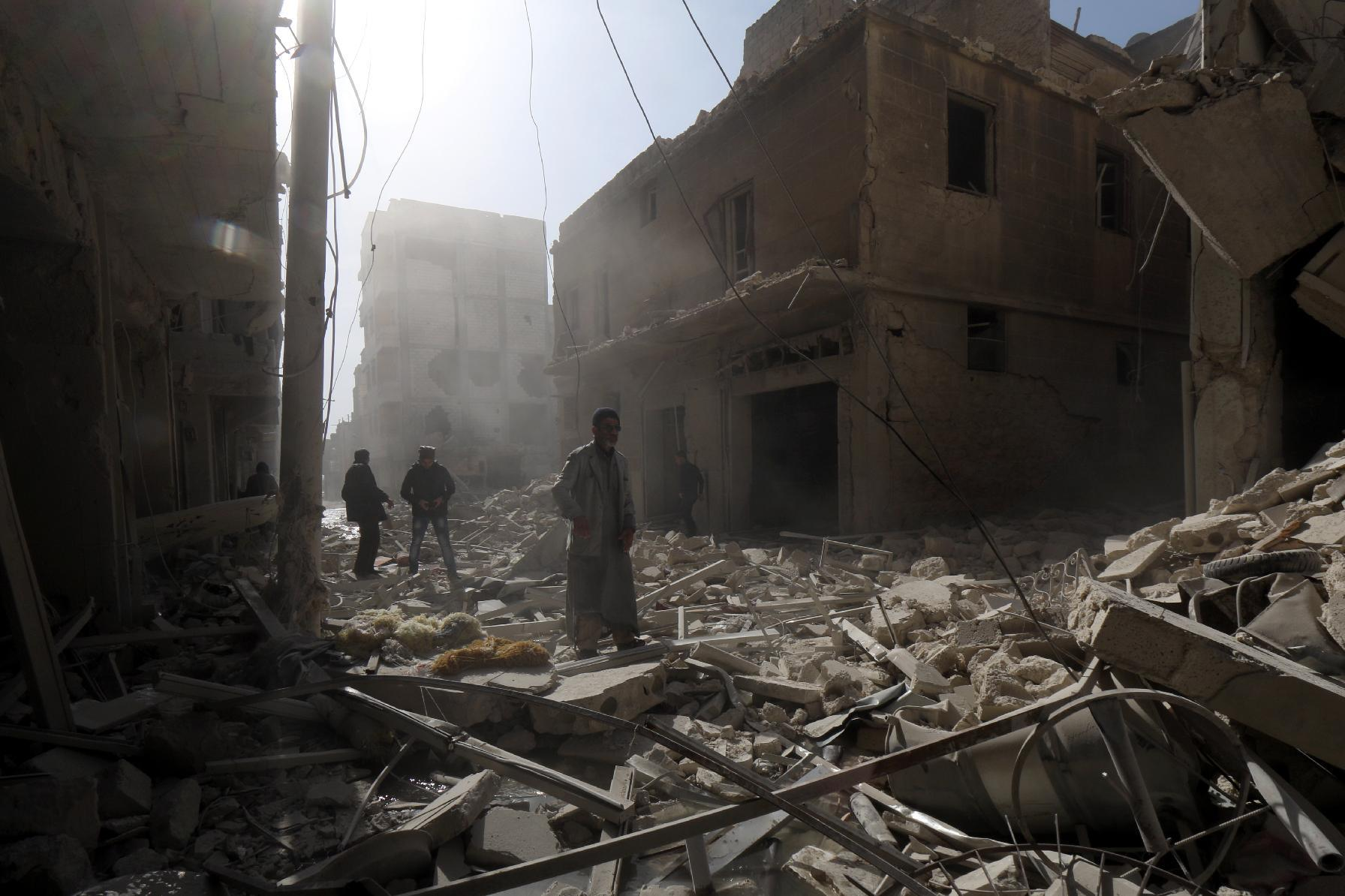 Syrians walk amid the rubble in search for survivors following a reported air strike by Syrian government forces in the Maysar neighbourhood of Aleppo on February 7, 2015 (AFP Photo/Zein Al-Rifai)