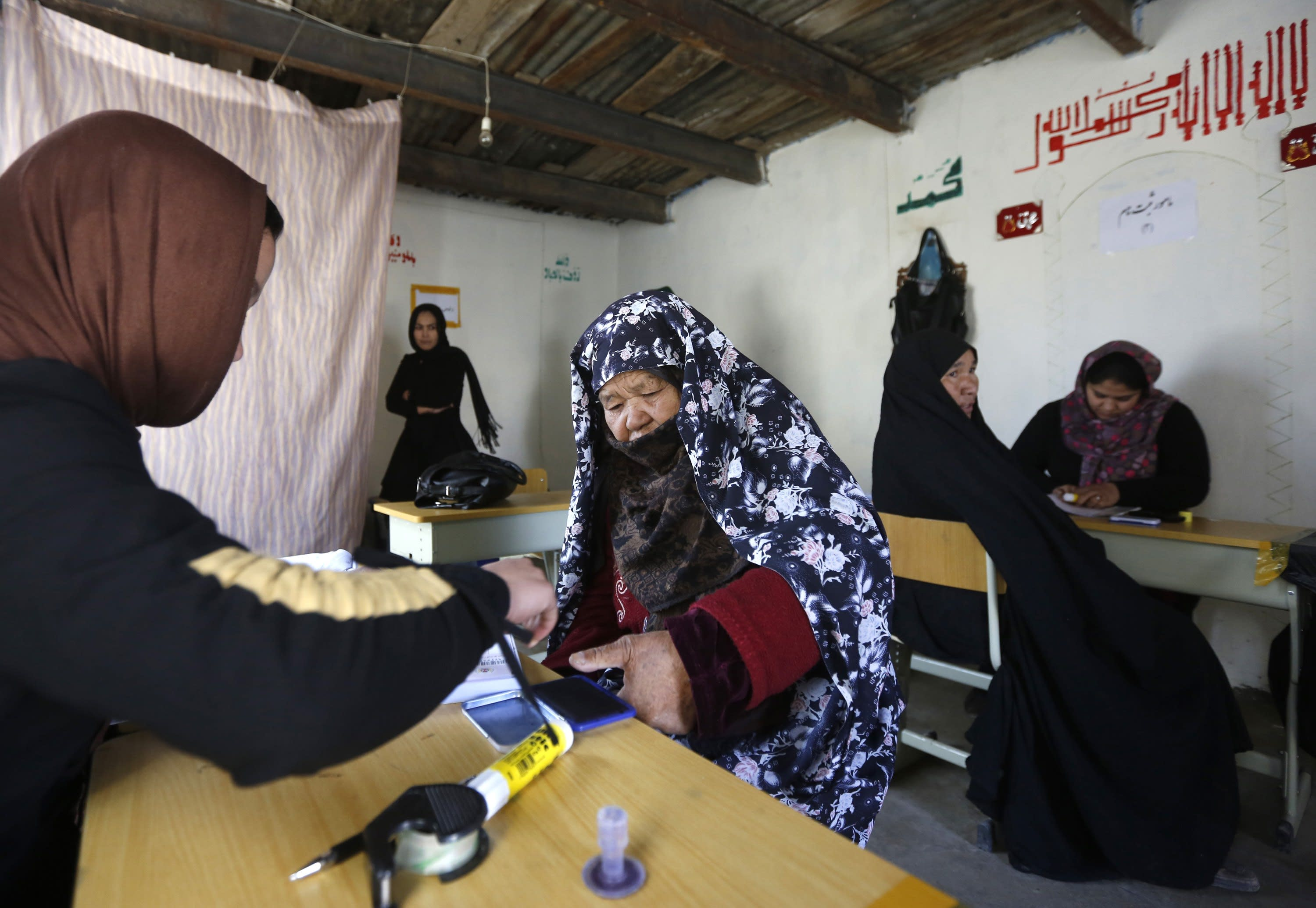 An Afghan woman puts her thumb print on her voter card at a registration centre in Kabul