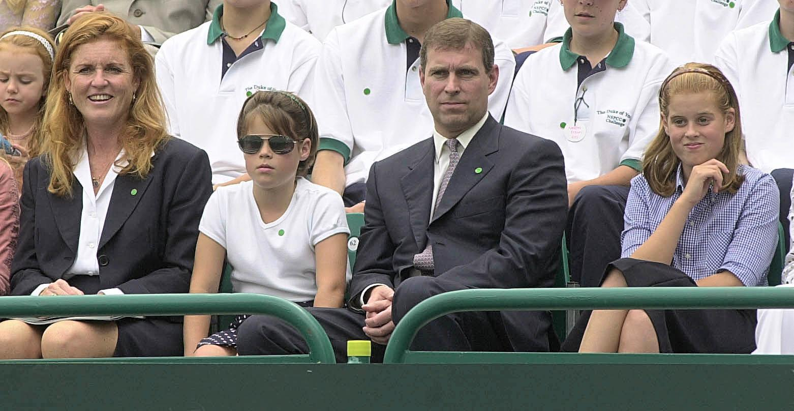 The Duke and Duchess of York sit with their children Beatrice (Left) and Eugenie (Right) while they await the start of the tennis in the grounds of Buckingham Palace. The Duke of York organised the charity tennis event, to raise money for the NSPCC.