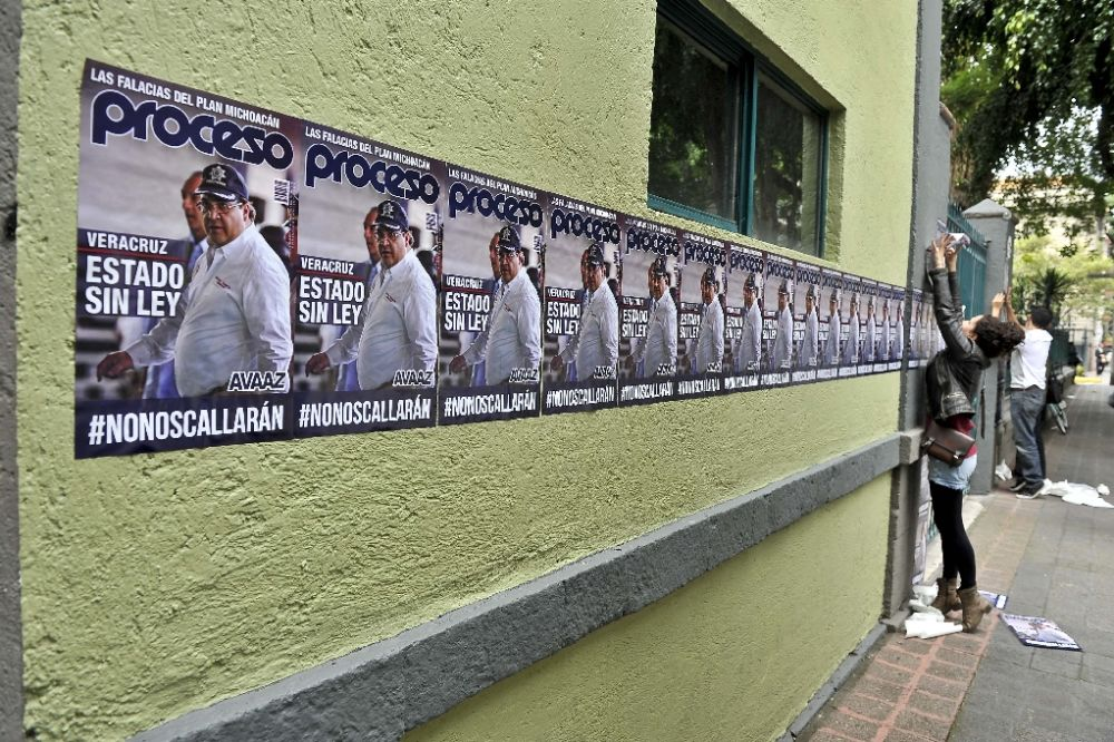 """An activist sticks posters with the image of Veracruz state governor Javier Duarte reading """"State without law"""" outside the representative office of the Veracruz state in Mexico City in August 2015"""