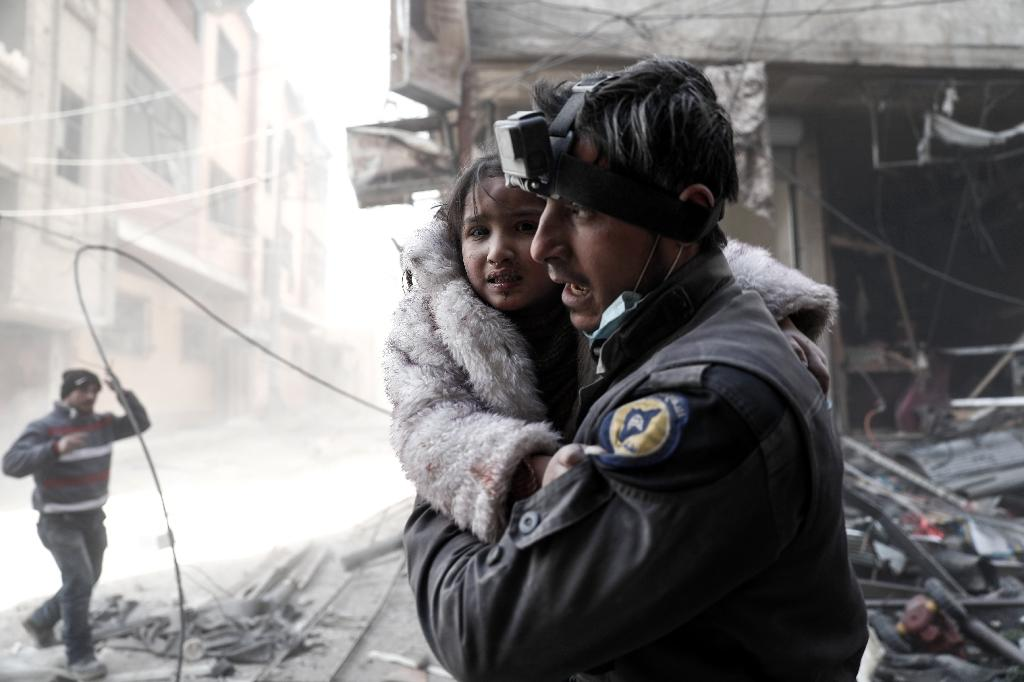 A Syrian White Helmets rescue worker carries a girl from the site of a government airstrike on the rebel-held town of Douma, on the eastern outskirts of Damascus, on February 25, 2017 (AFP Photo/Sameer Al-Doumy)