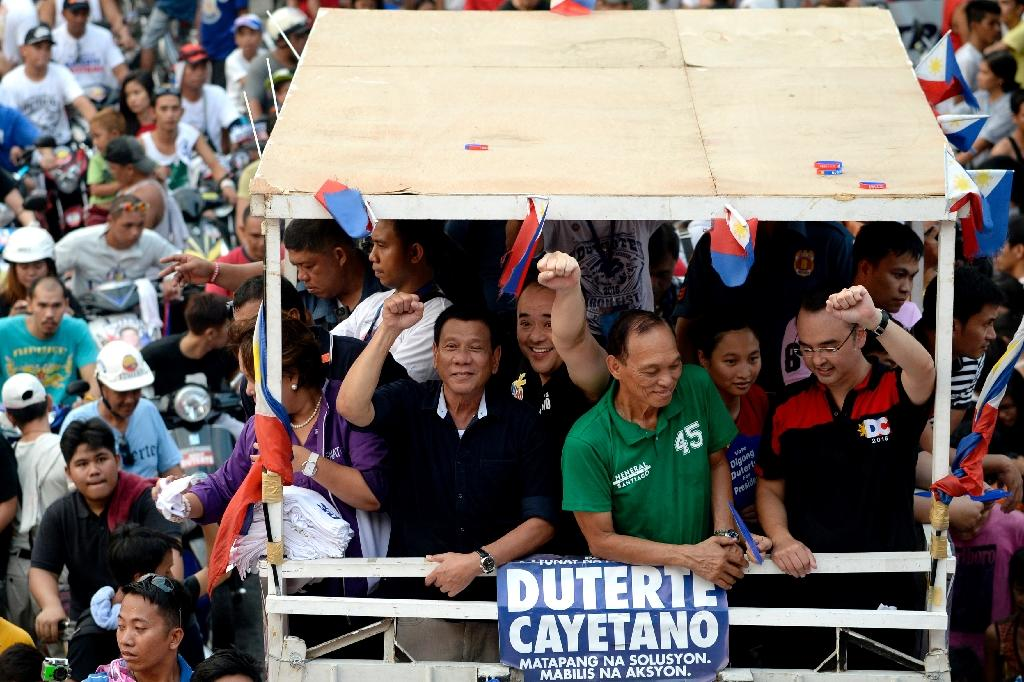 Philippine presidential candidate Rodrigo Duterte (centre L, in black) gestures to the crowd during a campaign motorcade near a port area in Manila (AFP Photo/Noel Celis)