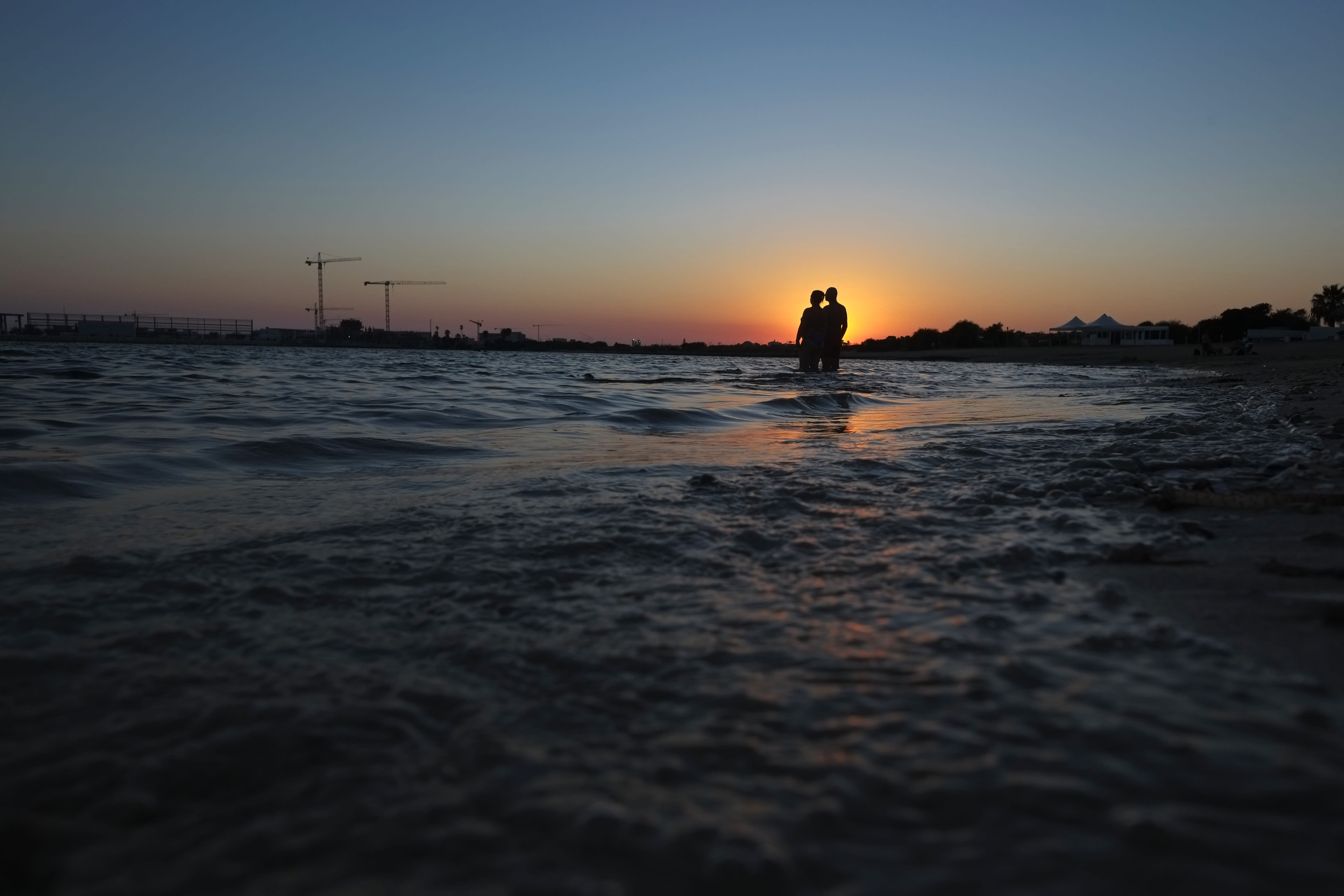 A couple stand in the sea during sunset in coastal resort of Ayia Napa in the eastern Mediterranean island of Cyprus, Saturday, Aug. 22, 2020. Meanwhile, Health Minister Constantinos Ioannou has extended until Jan. 15, 2021, a ban on outdoor festivals, concerts and exhibitions in places without seating where social distancing rules can't be enforced. (AP Photo/Petros Karadjias)
