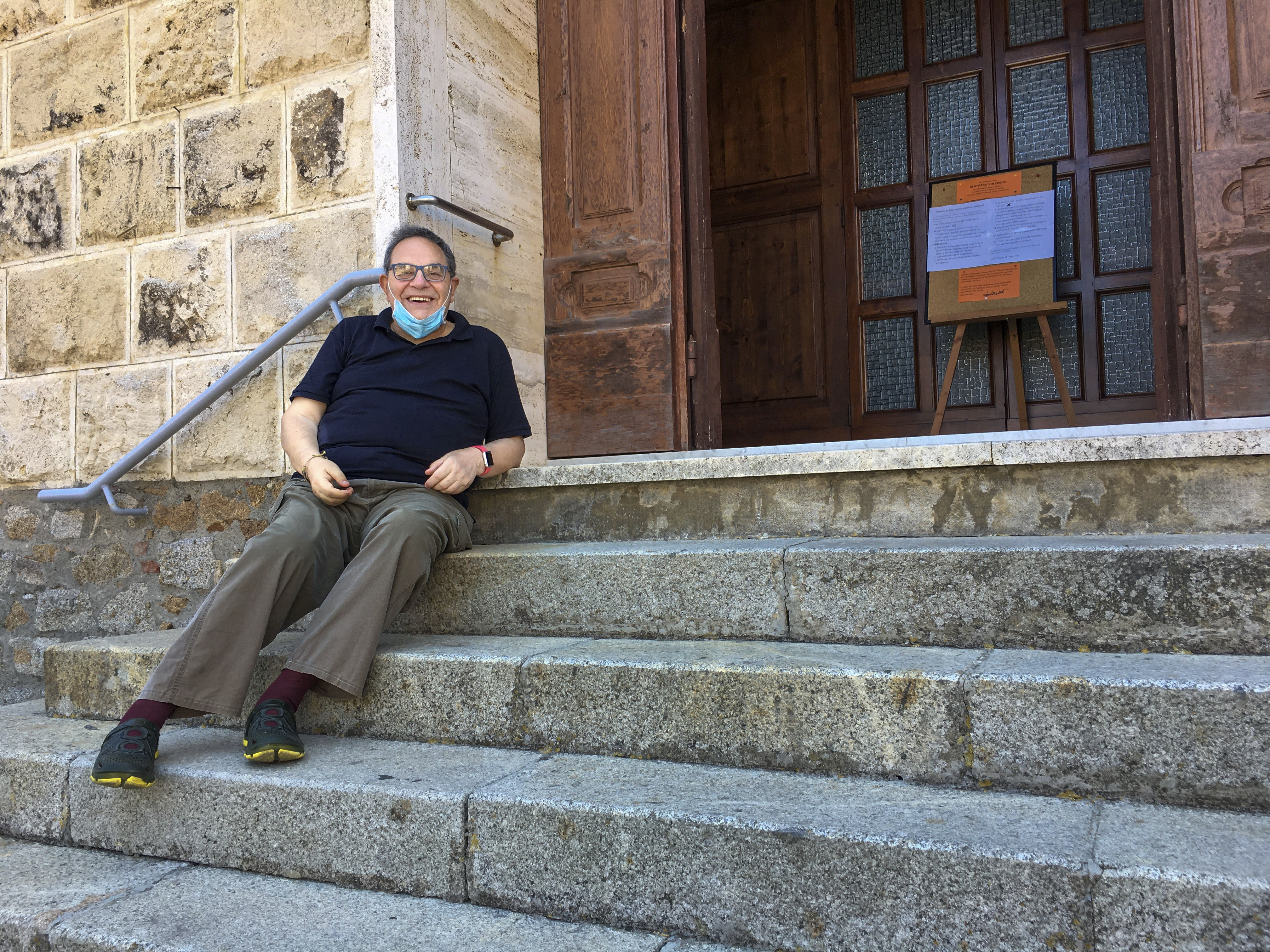"""Rev. Lorenzo Pasquotti poses for photos on the steps of his church at the Giglio Island, Italy, Wednesday, June 24, 2020y. Some 50 local mourners filled the pews for that funeral in Saints Lorenzo and Mamiliano Church, including a man from the continent that had COVID-19 infection, recalled the pastor, Rev. Pasquotti. """"After the funeral, there were greetings, hugging and kissing,"""" as always. Then came the procession to the cemetery, where """"there were more hugs and kisses."""" Yet, """"none of us had any sign"""" of COVID-19 in the days to follow, said Pasquotti. """"No one was sick. No symptoms that can make you think you were infected."""" (AP Photo/Paolo Santalucia)"""