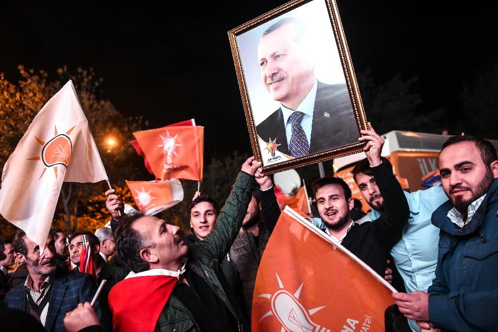 Supporters of Turkey's Justice and Development Party (AKP) hold up a portrait of Turkish President Recep Tayyip Erdogan as they celebrate in Istanbul after the first results in the country's general election on November 1, 2015 (AFP Photo/Ozan Kose)