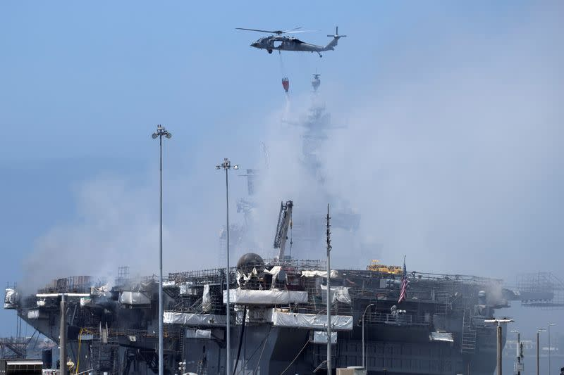 U.S. Navy helicopters continue fighting a fire on the amphibious assault ship USS Bonhomme Richard at Naval Base San Diego
