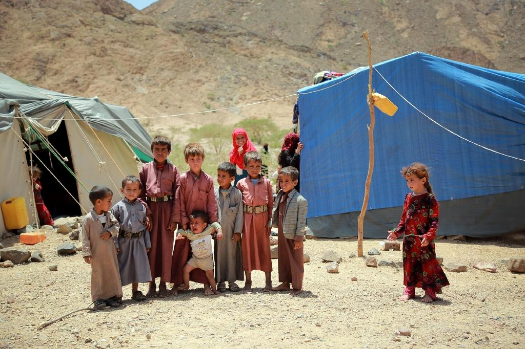 Yemeni children stand outside a tent at a makeshift camp for Internally Displaced Persons after they were forced to flee their homes due to the ongoing fighting in the country, in the Nehm region, west of Marib city, on May 8, 2016 (AFP Photo/Abdullah Al-Qadry)