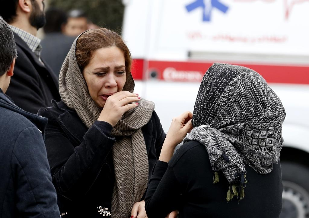 Relatives of passengers of Iran's Aseman Airlines doomed flight EP3704 react outside a mosque near Tehran's Mehrabad airport on February 18, 2018 (AFP Photo/ATTA KENARE)