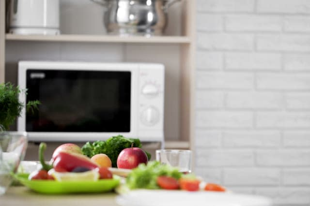 Kitchen view with microwave oven and fresh vegetables and fruit on the table
