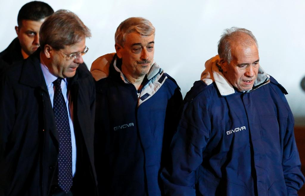 Gino Pollicardo (C) and Filippo Calcagno (R), two Italians kidnapped last July in Libya, are welcomed by Italy's Foreign Minister Paolo Gentiloni (L) at Ciampino airport in Rome on March 6, 2016