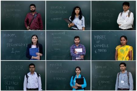 FILE PHOTO: unemployed people posing in front of a chalkboard with their qualifications during a job fair in Chinchwad