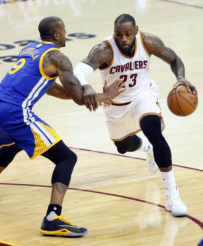 Cleveland Cavaliers forward LeBron James (R) drives to the basket against Golden State Warriors guard Andre Iguodala (L) during Game 6 of the NBA Finals in Cleveland, Ohio on June 16, 2016 (AFP Photo/Jay LaPrete)