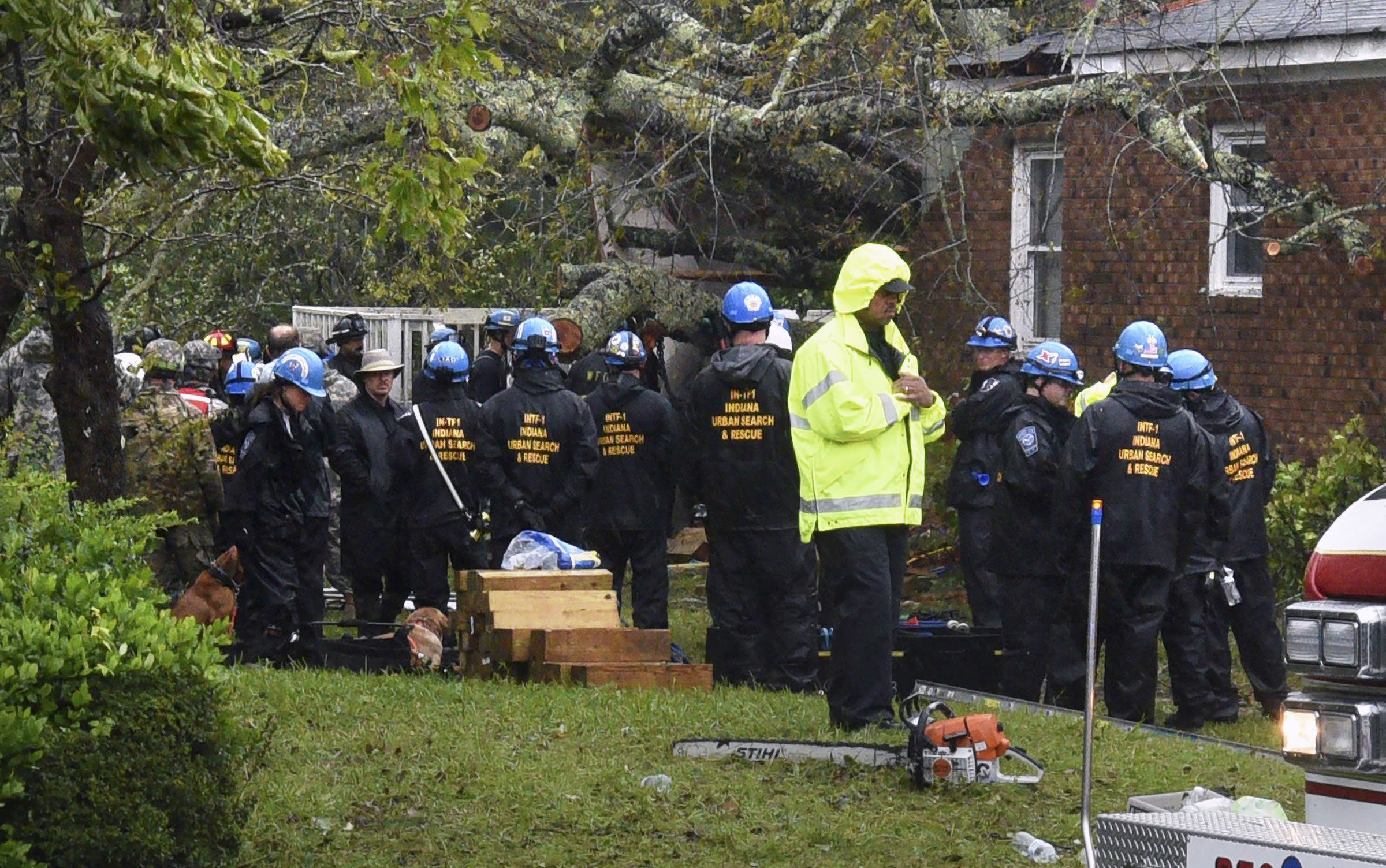 <p>Rescue workers, police and fire department members wait to remove the bodies of a mother and child who were killed by a falling tree as Hurricane Florence made landfall in Wilmington, N.C. Friday Sept. 14, 2018. The father was transported to the hospital with serious injuries. (Photo: Chuck Liddy/The News & Observer via AP) </p>