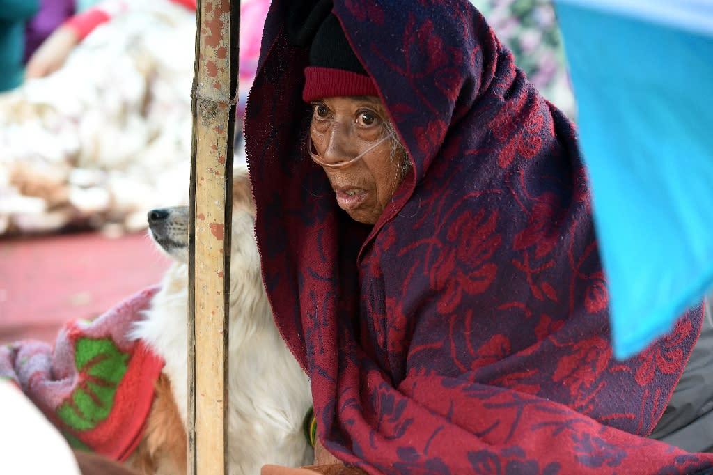Sanu Ranjitkar breathes oxygen from a cylinder under a makeshift shelter in Kathmandu (AFP Photo/Prakash Singh)