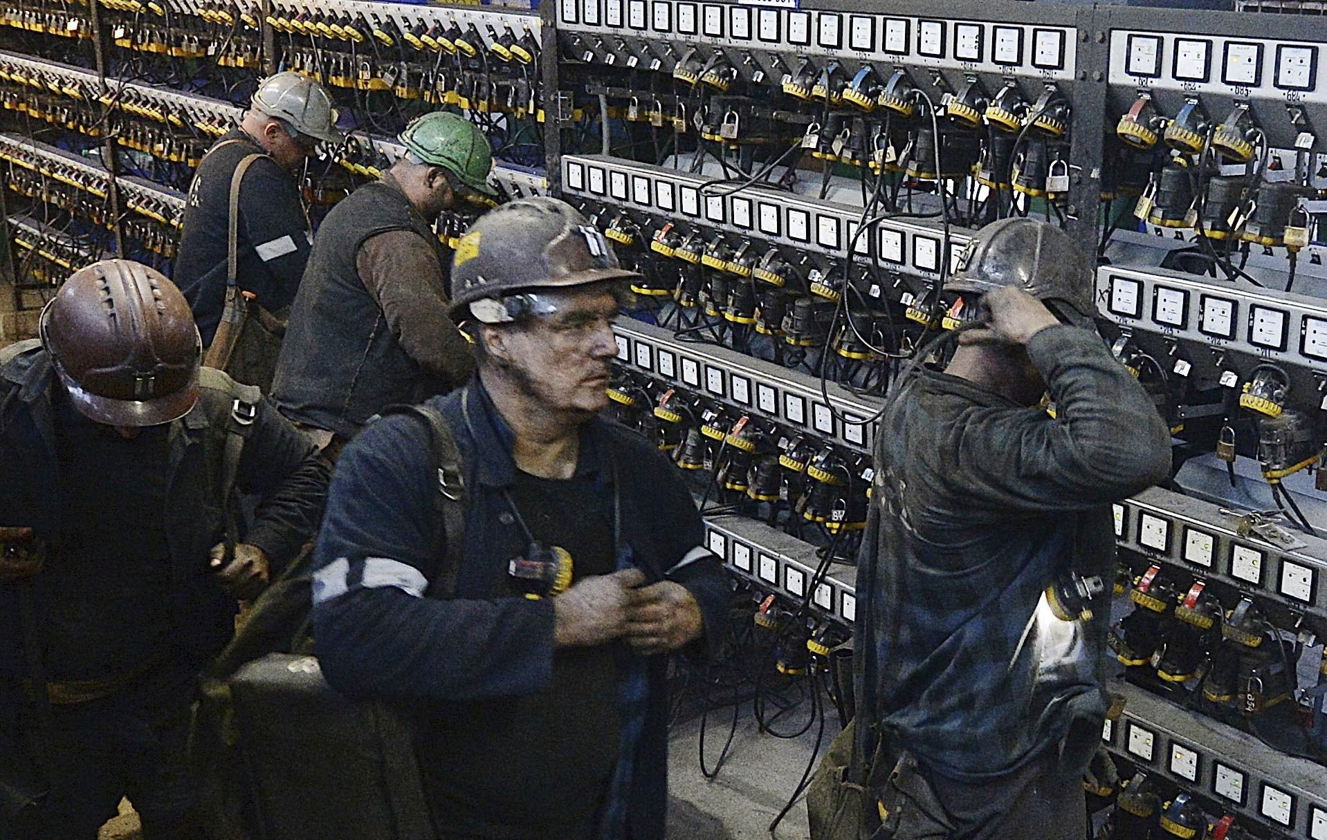 FILE - In this Nov. 21, 2018, file photo, miners put away their equipment after an underground shift at the Wujek coal mine in Katowice, in Poland's southern mining region of Silesia. The coronavirus has ripped through Poland's coal mines, where men descend deep underground in tightly packed elevators and work shoulder-to-shoulder. The virus hot spots, centered in the southern Silesia region, have paralyzed an already-troubled industry, forcing many to stay home from work and triggering a three-week closure of many state-run mines. (AP Photo/Czarek Sokolowski, File)