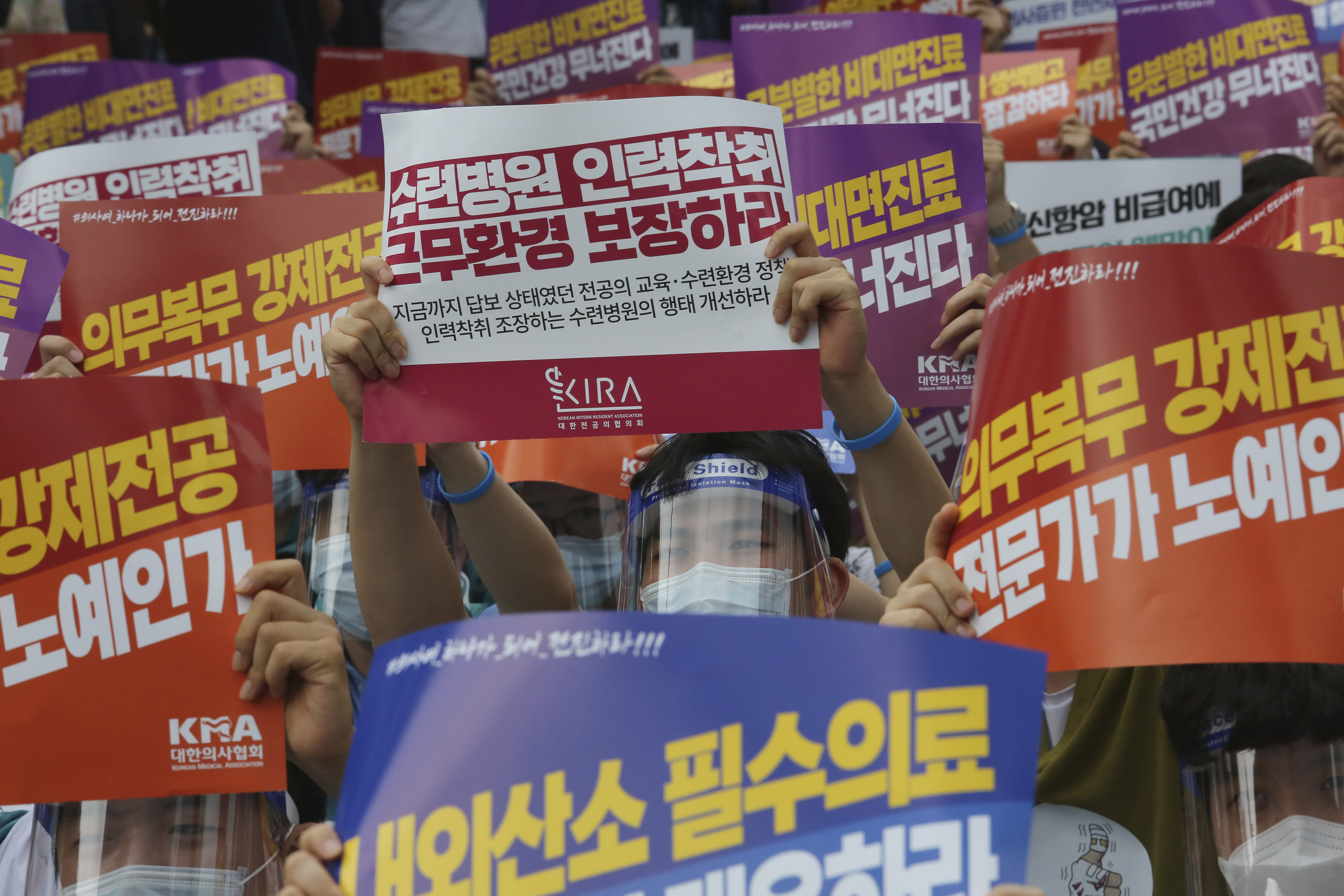 """A doctor holds up a placard during a rally against the government medical policy in Seoul, South Korea, Friday, Aug. 14, 2020. Thousands of doctors in South Korea began a strike Friday in protest of government medical policy, causing concerns about treatment of patients amid the coronavirus pandemic. The signs read: """"Ensure working conditions."""" (AP Photo/Ahn Young-joon)"""