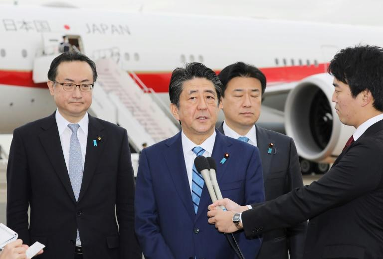 Japanese Prime Minister Shinzo Abe (C) speaks to the media before his departure at Tokyo's Haneda airport on Saturday for a three-country Gulf tour