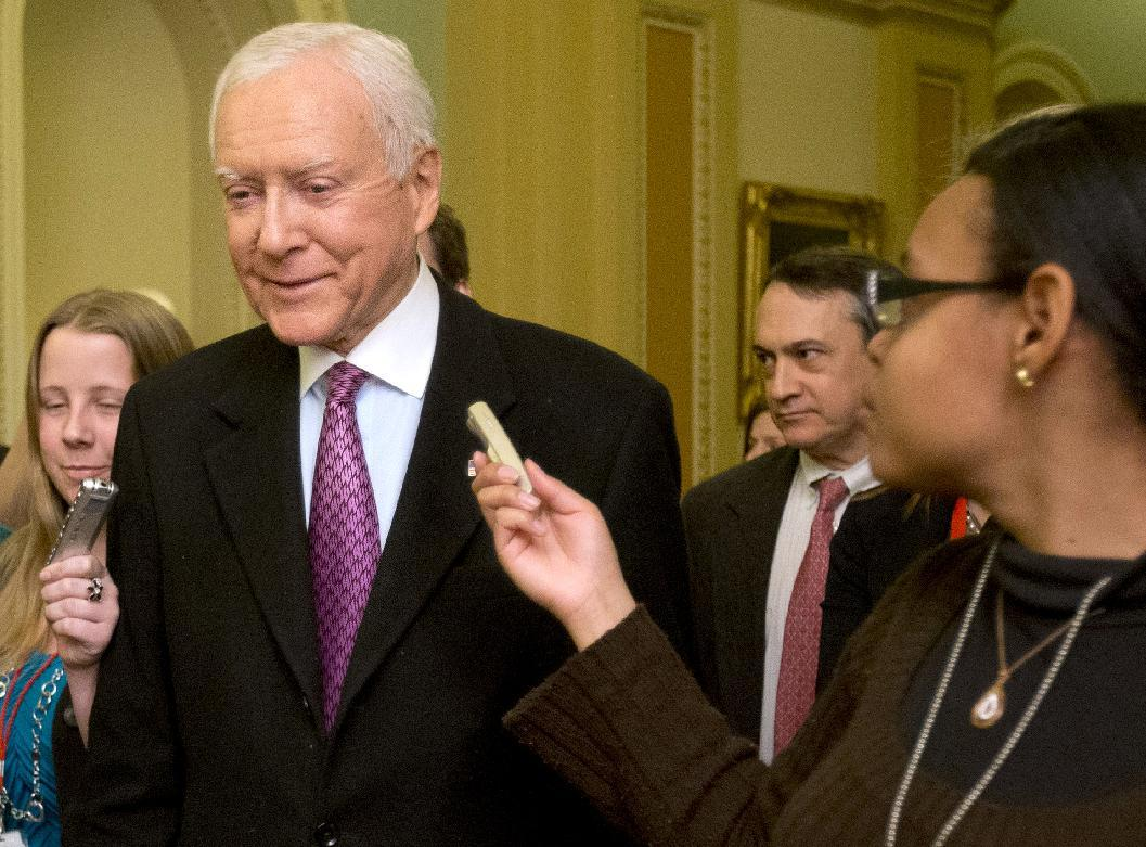 """FILE - In this Dec. 31, 2012 file photo, Sen. Orrin Hatch, R-Utah, center, fields questions from reporters as he walks on Capitol Hill in Washington. Foreigners leaving the country through any of the nation's 30 busiest airports would undergo mandatory fingerprinting under an amendment senators added Monday to a sweeping immigration bill. """"This is an agreement that we need to build toward a biometric visa exit system,"""" said Sen. Jeff Flake, R-Ariz., who offered the amendment by Hatch, who was absent Monday. """"Implementing this biometric exit system is long overdue."""" (AP Photo/Jacquelyn Martin, File)"""