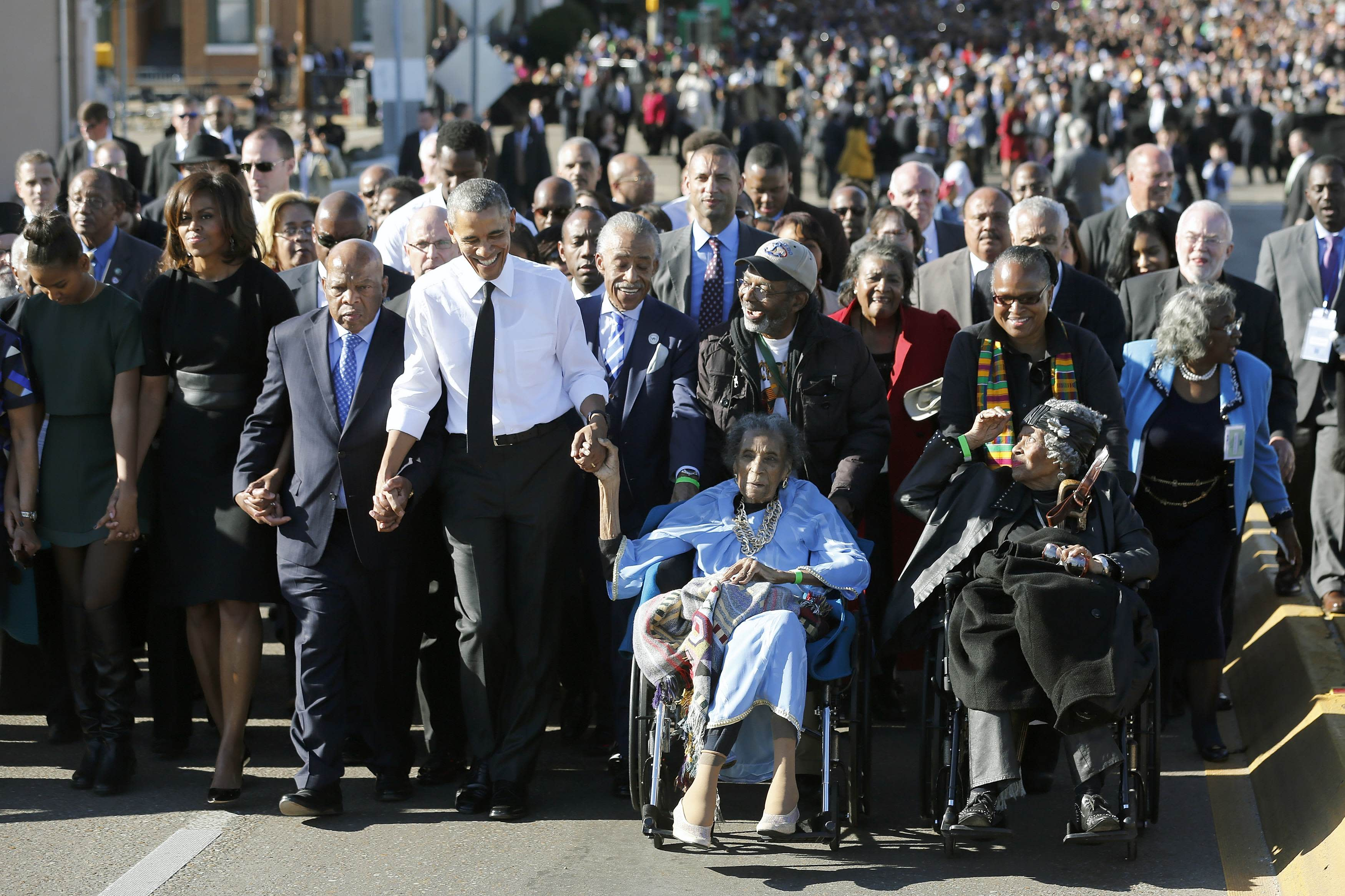 U.S. President Barack Obama (4th L) participates in a march with civil rights movement veterans across the Edmund Pettus Bridge in Selma, Alabama, March 7, 2015. Also pictured are first lady Michelle Obama (2nd L) and U.S. Representative John Lewis (D-GA) (3rd L), who was beaten by police on the bridge as a young man. The event comes on the 50th anniversary of the 'Bloody Sunday' march at the bridge, where police and state troopers beat and used tear gas against peaceful marchers who were advocating against racial discrimination at the voting booth. REUTERS/Jonathan Ernst (UNITED STATES - Tags: POLITICS ANNIVERSARY SOCIETY)