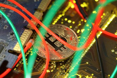 Representation of the Bitcoin virtual currency standing on the PC motherboard is seen in this illustration picture