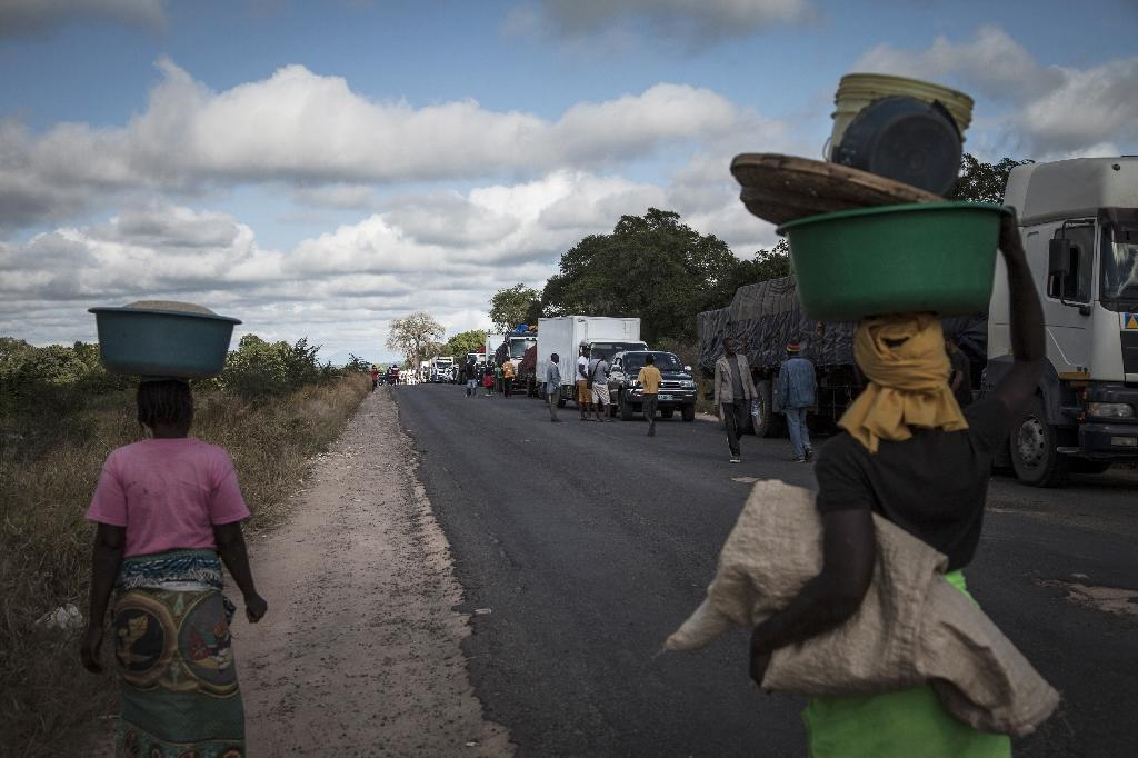 Street vendors sell to drivers along Mozambique's main north-south road as they wait for a military escort to provide protection for trucks and travellers (AFP Photo/John Wessels)