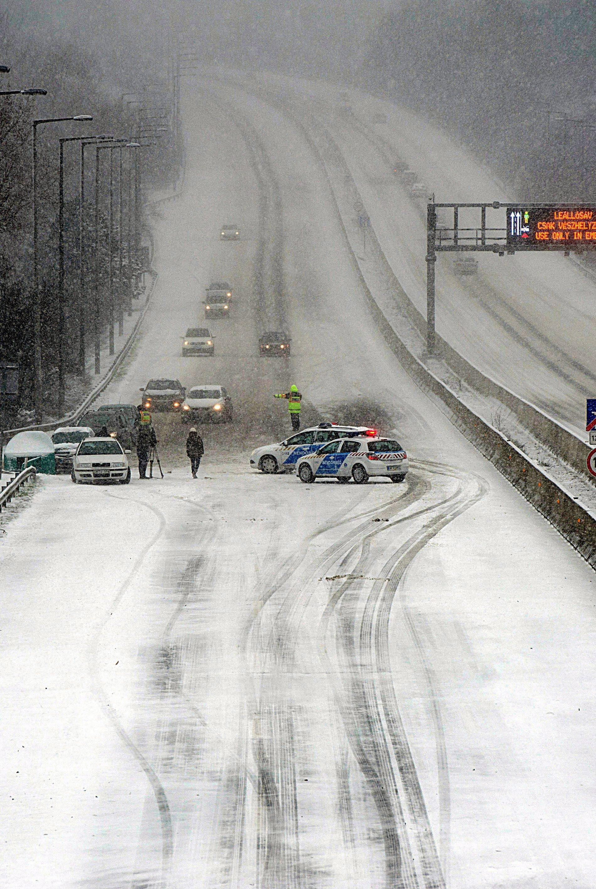 Due to a heavy snowstorms, police seal off a section of a highway in the suburbs of Budapest, Hungary, Friday March 15 2013. Winter weather returning to Hungary with heavy snowfall, blizzards, ice and cold has left thousands without electricity, blocked access to several localities, forced traffic halts in major services and caused several accidents across the country. (AP Photo/MTI, Peter Lakatos)