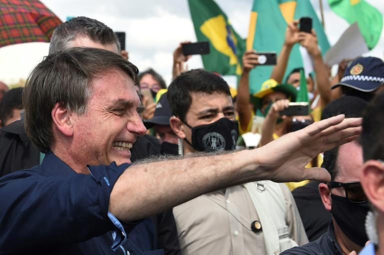 Brazil's President Jair Bolsonaro greets supporters upon arrival at Planalto Palace in Brasilia, on May 24, 2020, amid the COVID-19 coronavirus pandemic
