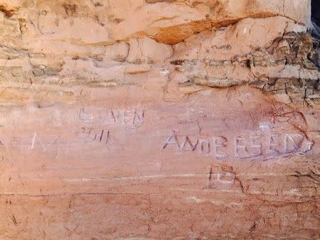Graffiti is seen scratched into a sandstone wall near Frame Arch in Arches National Park near Moab, Utah