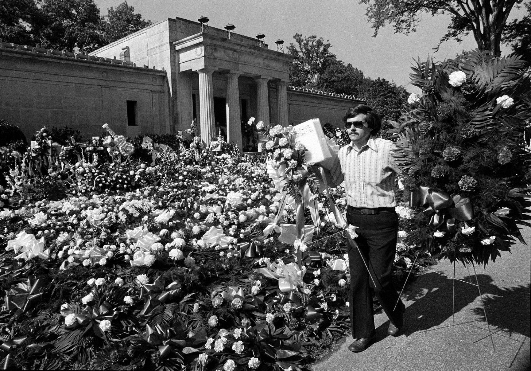 """FILE - In this Aug. 18, 1977 file photo, a florist adds more floral arrangements to the overflowing collection of flowers that cover the ground at the mausoleum where singer Elvis Presley will be entombed during funeral services today in Memphis, Tenn. Celebrity auctioneer Darren Julien says the crypt inside the granite and marble mausoleum where Presley was originally entombed at the Forest Hill Cemetery in Memphis, Tenn., will be part of his """"Music Icons"""" auction on June 23 and 24, 2012, in Beverly Hills, Calif. (AP Photo, File)"""