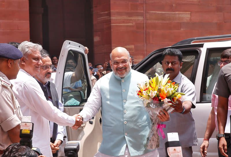 FILE PHOTO: India's newly appointed Home Minister Amit Shah receives a flower bouquet upon his arrival at the home ministry in New Delhi