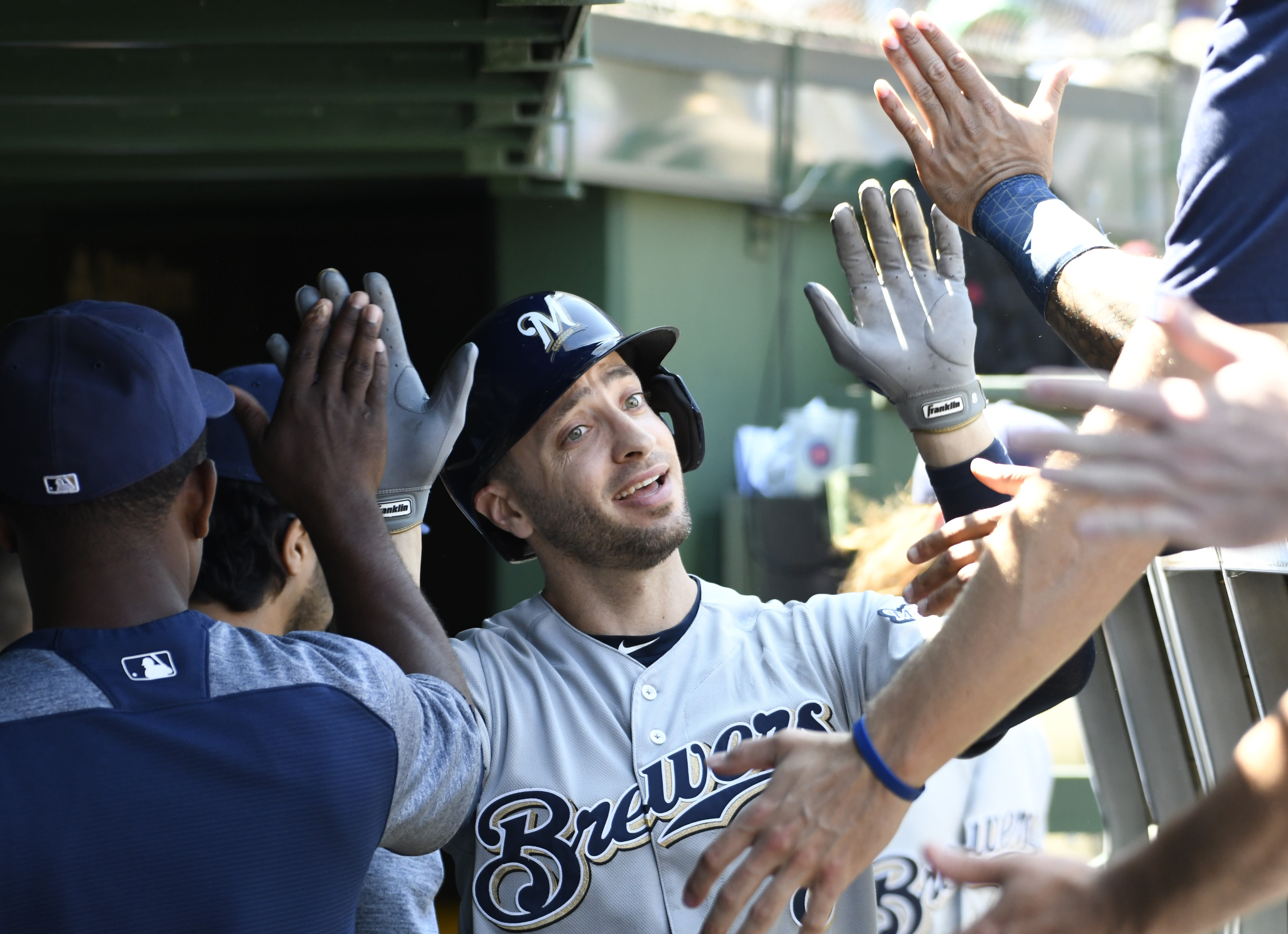 Milwaukee Brewers' Ryan Braun, center, is greeted in the dugout after hitting a home run against the Chicago Cubs during the second inning of a baseball game, Friday, Aug. 2, 2019, in Chicago. (AP Photo/David Banks)
