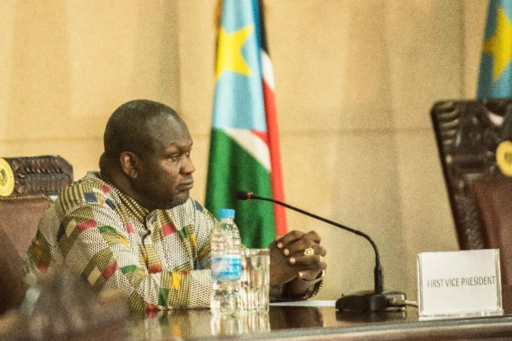 South Sudan's former rebel leader and new vice-president Riek Machar listens as the president (not pictured) delivers a statement during a ceremony at the Presidential House in Juba on April 26, 2016 (AFP Photo/Charles Lomodong)